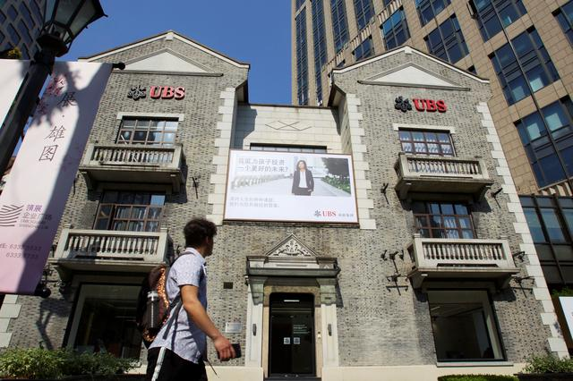 FILE PHOTO: A man walks past a building of Swiss bank UBS in Shanghai, China May 22, 2019. Picture taken May 22, 2019. REUTERS/Stringer