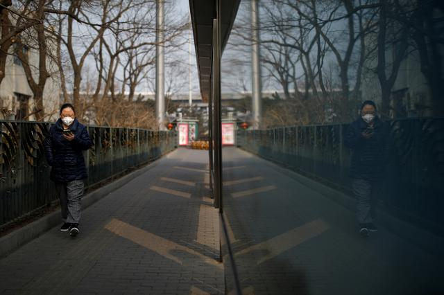A woman looks at her cellphone while she walks next to a bus stop, as the country is hit by an outbreak of the new coronavirus, in Beijing, China January 27, 2020. REUTERS/Carlos Garcia Rawlins