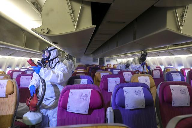 Members of the Thai Airways crew disinfect the cabin of an aircraft of the national carrier during a procedure to prevent the spread of the coronavirus at Bangkok's Suvarnabhumi International Airport, Thailand, January 28, 2020. REUTERS/Athit Perawongmetha