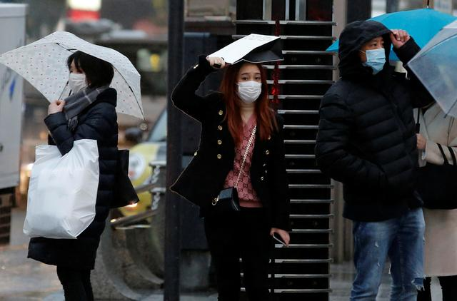 Pedestrians wearing masks stand in front of a crosswalk at a shopping district in Tokyo, Japan, January 28, 2020. REUTERS/Kim Kyung-Hoon