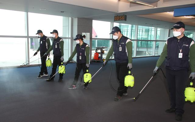 FILE PHOTO: Employees from a disinfection service company sanitize the floor of Incheon International Airport in Incheon, South Korea, January 24, 2020. Yonhap via REUTERS
