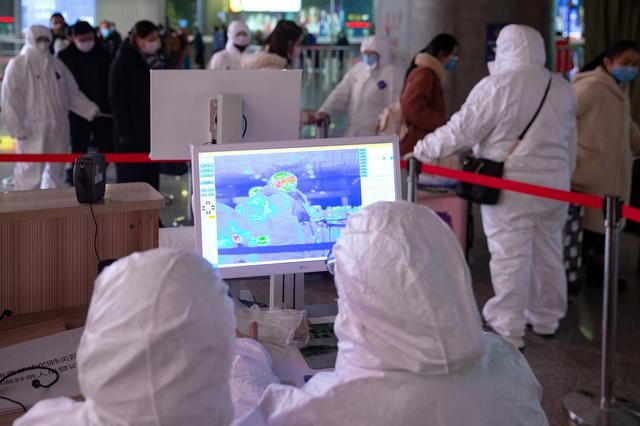 FILE PHOTO: Workers in protective suits monitor a screen showing the thermal scan to check temperatures of passengers arriving at the Nanjing Railway Station, following the outbreak of a new coronavirus, during Chinese Lunar New Year holiday in Nanjing, China January 27, 2020. cnsphoto via REUTERS