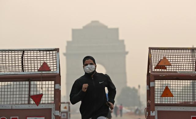 FILE PHOTO: A man wearing a mask runs past the India Gate on a smoggy morning in New Delhi, India, October 28, 2019 REUTERS/Adnan Abidi