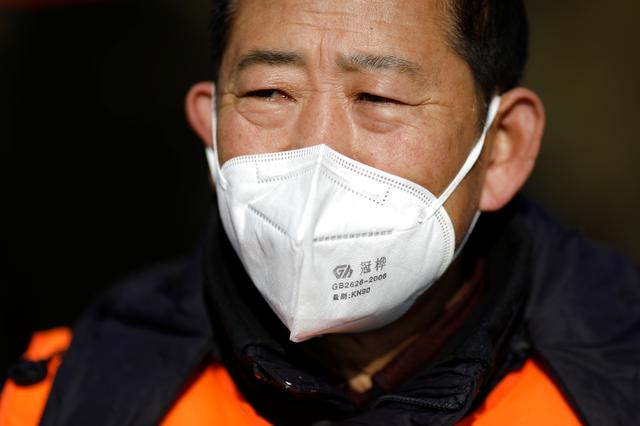 A village committee member wears face mask and vest as he guards at the entrance of a community to prevent outsiders from entering, as the country is hit by an outbreak of the new coronavirus, in Tianjiaying village, outskirts of Beijing, China January 29, 2020. REUTERS/Carlos Garcia Rawlins