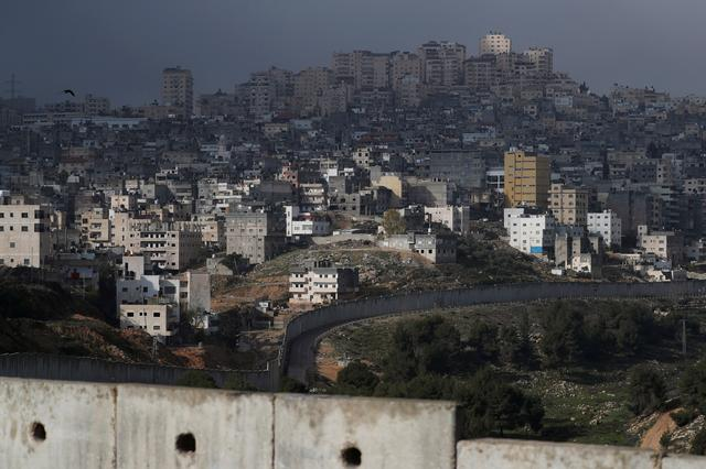 The Shuafat refugee camp in East Jerusalem is seen behind the Israeli barrier, in an area Israel annexed to Jerusalem after capturing it in the 1967 Middle East war January 29, 2020. REUTERS/Ammar Awad