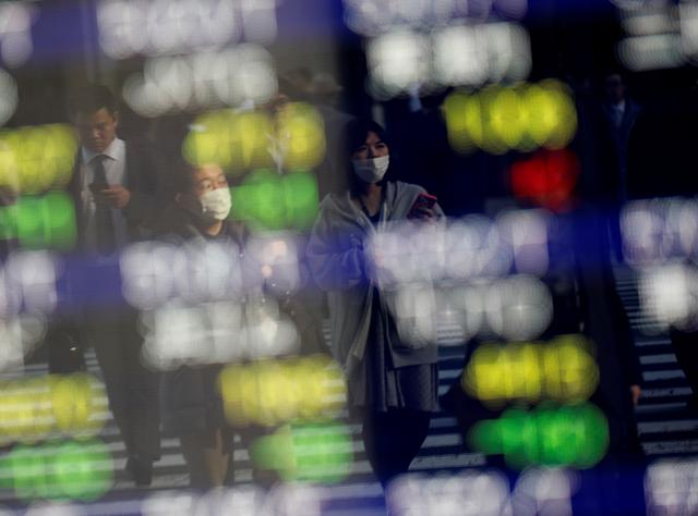 FILE PHOTO: Pedestrians wearing facial masks are reflected on an electric board showing stock prices outside a brokerage at a business district in Tokyo, Japan January 30, 2020. REUTERS/Kim Kyung-Hoon