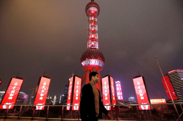 """A man wearing a face mask walks past the Oriental Pearl Tower lit with messages reading """"Stay strong China"""", on the Lantern Festival, which marks the end of the Chinese Lunar New Year celebrations, following an outbreak of the novel coronavirus in the country, in Shanghai, China February 8, 2020. Picture taken February 8, 2020. cnsphoto via REUTERS"""