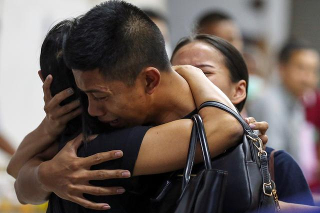 Son and daughter of Captain Siriwiwat Sangprasita, a victim of a gun battle involving a Thai soldier on a shooting rampage, cry after seeing his dead body at a hospital in Nakhon Ratchasima, Thailand, February 9, 2020. REUTERS/Athit Perawongmetha