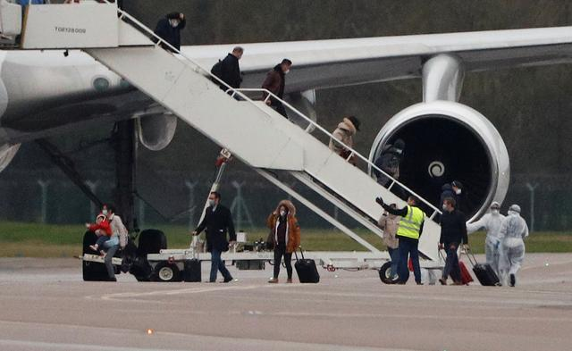 Passengers from China disembark from a plane at RAF Brize Norton near Oxford, Britain, February 9, 2020. REUTERS/Peter Nicholls