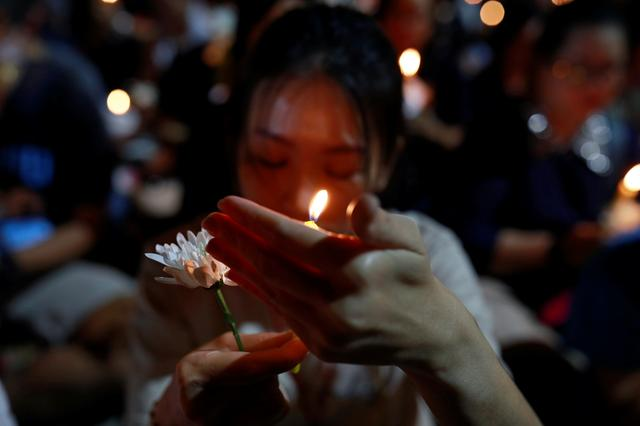 A woman holds a candle light as she prays for victims who died in mass shooting, involving a Thai soldier on a shooting rampage, in Nakhon Ratchasima, Thailand February 9, 2020. REUTERS/Soe Zeya Tun