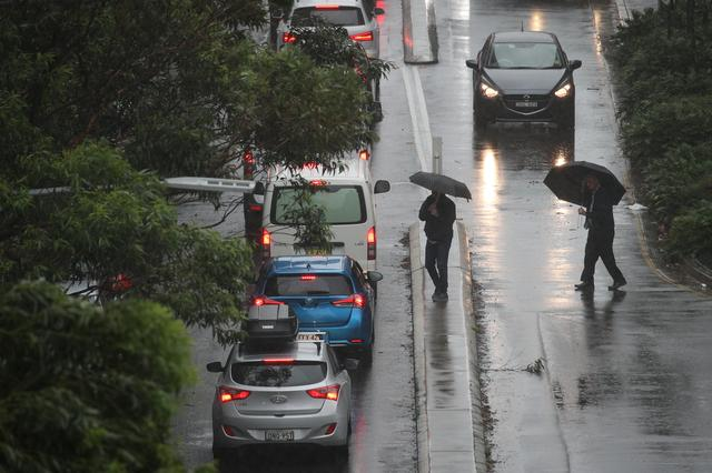 Pedestrians brave strong wind and rain in Sydney, New South Wales, Australia, February 9, 2020.  REUTERS/Loren Elliott