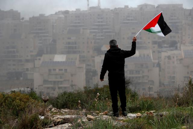 A demonstrator holds a Palestinian flag as the Jewish settlement of Modiin Illit is seen in the background, during a protest against the U.S. President Donald Trump's Middle East peace plan, in the village of Bilin in the Israeli-occupied West Bank February 7, 2020. Picture taken February 7, 2020. REUTERS/Mohamad Torokman