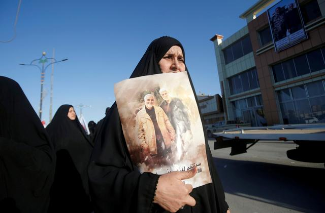 FILE PHOTO: An Iraqi woman holds a picture of Iranian Major-General Qassem Soleimani, head of the elite Quds Force, and Iraqi militia commander Abu Mahdi al-Muhandis, who were killed in an air strike at Baghdad airport, during a funeral procession for militia commander Abu Mahdi al-Muhandis, in Basra, Iraq, January 7, 2020. REUTERS/Essam al-Sudani/File Photo