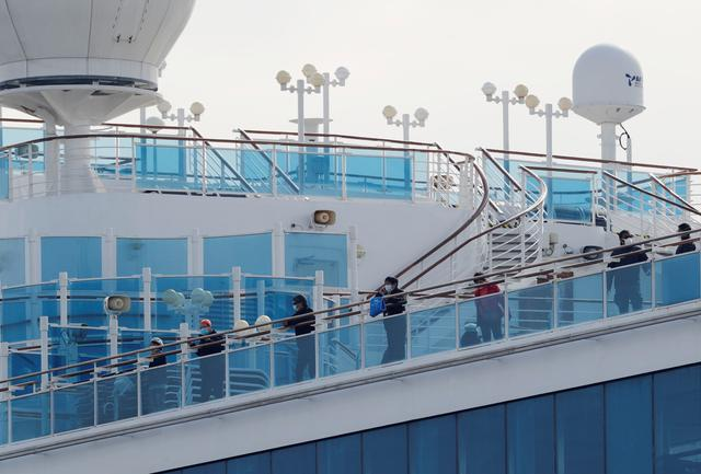Passengers look out from a deck of the cruise ship Diamond Princess at Daikoku Pier Cruise Terminal in Yokohama, south of Tokyo, Japan February 12, 2020. REUTERS/Kim Kyung-hoon