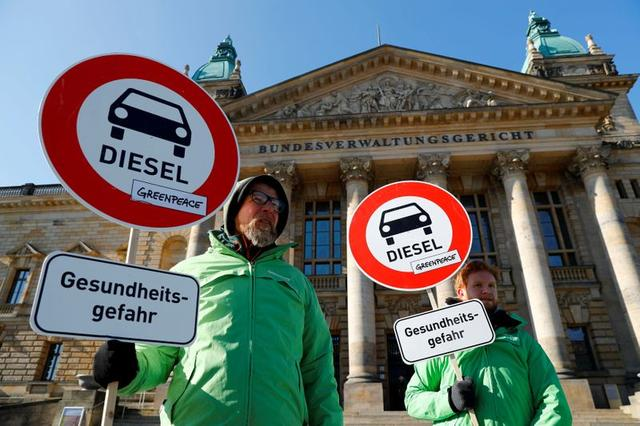 """FILE PHOTO: Greenpeace activists demonstrate in favour of cities banning diesel cars to help reduce air pollution, in Leipzig, Germany, February 27, 2018. The placards read: """"Health risk."""" REUTERS/Fabrizio Bensch"""