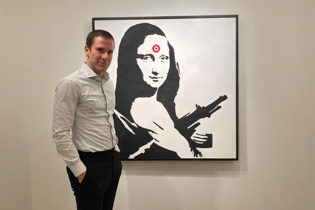 FILE PHOTO: Scott Lynn, CEO and founder of Masterworks, poses next to a Banksy artwork in New York, U.S., February 11, 2020.  REUTERS/Aleksandra Michalska