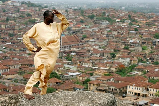FILE PHOTO: Yinka Sotomi stands atop Oluma Rock, a spiritual site for the Yoruba tribe, overlooking the city of Abeokuta in southern Nigeria, April 16, 2007. REUTERS/Finbarr O'Reilly/File Photo
