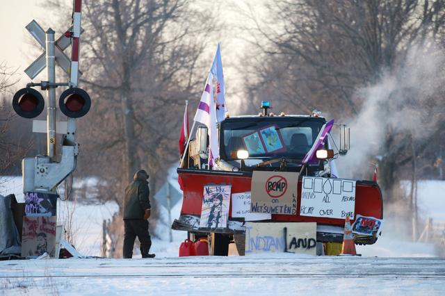 A man passes a snowplow in -23 Celsius (-9 Fahrenheit) temperatures at the camp of First Nations members of the Tyendinaga Mohawk Territory who continue to block Canadian National Railway (CN Rail) train tracks as part of a protest against British Columbia's Coastal GasLink pipeline, in Tyendinaga, Ontario, Canada, February 14, 2020.   REUTERS/Chris Helgren