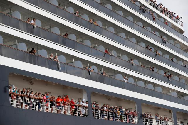 Passengers wave their towels as they are about to leave MS Westerdam, a cruise ship that spent two weeks at sea after being turned away by five countries over fears that someone aboard might have the coronavirus, as it docks in Sihanoukville, Cambodia February 14, 2020.  REUTERS/Soe Zeya Tun