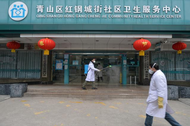 FILE PHOTO: A doctor disinfects the entrance of a community health service center, which has an isolated section to receive patients with mild symptoms caused by the novel coronavirus and suspected patients of the virus, in Qingshan district of Wuhan, Hubei province, China February 2, 2020. Picture taken February 2, 2020. China Daily via REUTERS