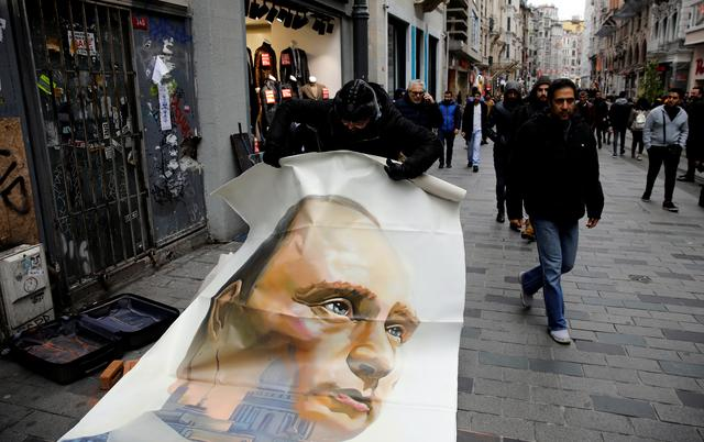 Russian artist and former mayor of Arkhangelsk Alexander Donskoy picks up a portrait of Russian President Vladimir Putin at Istiklal Street in Istanbul, Turkey February 15, 2020. REUTERS/Umit Bektas