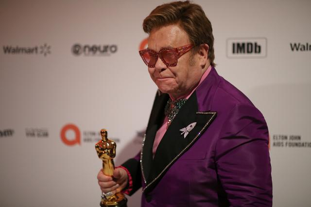"FILE PHOTO: Elton John attends the 28th Annual Elton John AIDS Foundation Academy Awards Viewing Party,  holding the Oscar for Best Original Song for ""(I'm Gonna) Love Me Again"" from ""Rocketman"", which he won with Bernie Taupin at the 92nd Academy Awards, in West Hollywood, California, U.S. February 9, 2020.  REUTERS/David McNew"