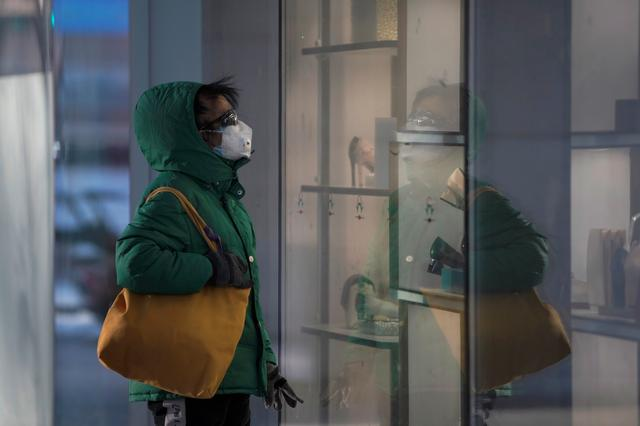 A woman wearing a face mask looks at a shopping window as the country is hit by an outbreak of the novel coronavirus, in Beijing's central business district, China February 16, 2020. REUTERS/Stringer