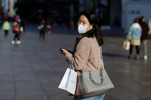 FILE PHOTO: A woman wearing a mask is seen at a main shopping area, in downtown Shanghai, China, as the country is hit by an outbreak of a new coronavirus, February 16, 2020. REUTERS/Aly Song