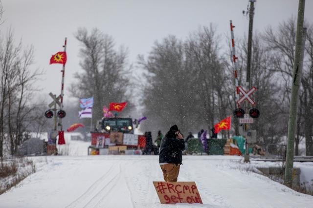 FILE PHOTO: A man with a sign stands near the site of a rail stoppage on Tyendinaga Mohawk Territory, as part of a protest against British Columbia's Coastal GasLink pipeline, in Tyendinaga, Ontario, Canada February 15, 2020.   REUTERS/Carlos Osorio/File Photo