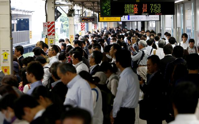 FILE PHOTO:  Passengers wait for a train on a platform at a station in Kawasaki, Japan, June 14, 2017. REUTERS/Kim Kyung-Hoon/File Photo