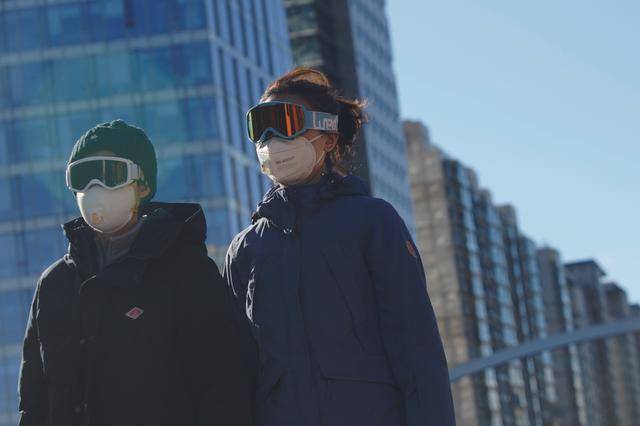 People wearing snow goggles and face masks are seen on a street, as the country is hit by an outbreak of the novel coronavirus, in Beijing's central business district, China February 16, 2020. REUTERS/Stringer