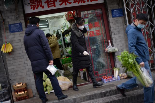 Residents buy food in a greengrocer's shop at a hutong, as the country is hit by an outbreak of the novel coronavirus, in Beijing, China February 18, 2020. REUTERS/Tingshu Wang