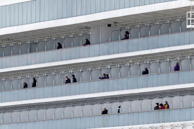 Passengers look out from the cruise ship Diamond Princess at Daikoku Pier Cruise Terminal in Yokohama, south of Tokyo, Japan February 19, 2020. REUTERS/Kim Kyung-hoon