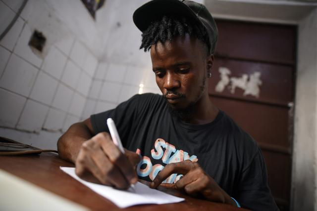 """Yousef Kamara works on a poem in the Way Out media center's """"Writers Room"""" in Freetown, Sierra Leone February 11, 2020. Picture taken February 11, 2020. REUTERS/Cooper Inveen"""