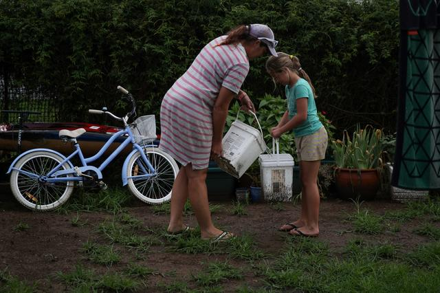 Eight-year-old Chelsea Symonds helps her mother Sally Roser to water plants in their yard with buckets of collected rainwater in the drought-affected town of Murrurundi, New South Wales, Australia February 17, 2020.   REUTERS/Loren Elliott