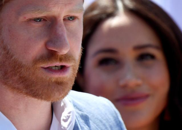 FILE PHOTO: Britain's Prince Harry, Duke of Sussex, gives a speech as his wife Meghan, Duchess of Sussex, looks on, during a visit to the Youth Employment Services (YES) Hub in Tembisa township, near Johannesburg, South Africa, October 2, 2019. REUTERS/Toby Melville
