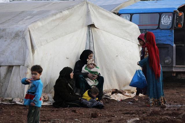 Internally displaced people sit outside tents at a makeshift camp in Azaz, Syria February 19, 2020.  REUTERS/Khalil Ashawi