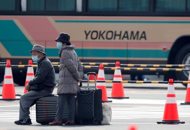 Passengers wait for transportation after leaving the coronavirus-hit Diamond Princess cruise ship docked at Yokohama Port, south of Tokyo, Japan, February 20, 2020. REUTERS/Kim Kyung-Hoon