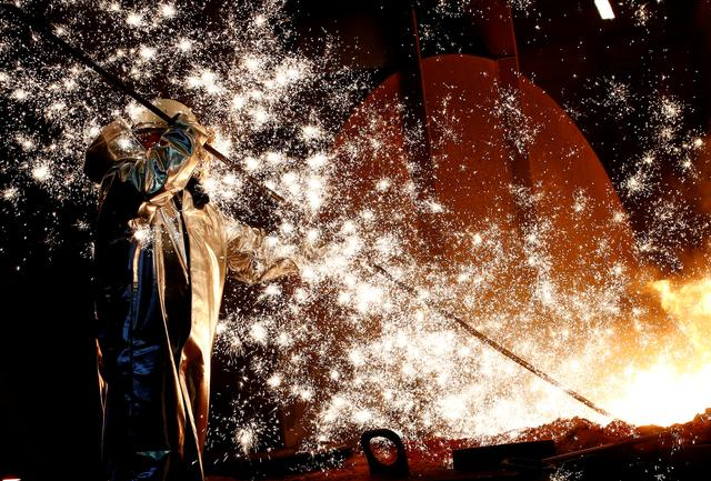 FILE PHOTO: A steel worker of Germany's industrial conglomerate ThyssenKrupp AG stands a mid of emitting sparks of raw iron from a blast furnace at Germany's largest steel factory in Duisburg, Germany. Picture taken January, 28, 2019.    REUTERS/Wolfgang Rattay/File Photo