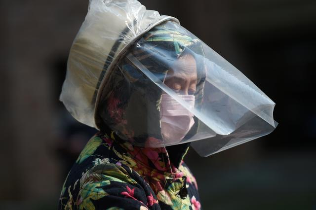 A resident wears a makeshift protective face shield at a residential compound in Wuhan, the epicentre of the novel coronavirus outbreak, Hubei province, China February 21, 2020. REUTERS/Stringer
