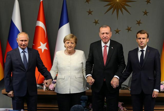 FILE PHOTO: German Chancellor Angela Merkel, Russian President Vladimir Putin, Turkish President Tayyip Erdogan and French President Emmanuel Macron hold hands at a news conference after a Syria summit, in Istanbul, Turkey October 27, 2018. Emrah Yorulmaz/Pool via REUTERS
