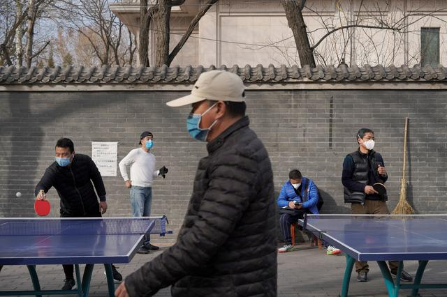 People wearing face masks play table tennis at a park, following an outbreak of the novel coronavirus in the country, in Beijing, China February 21, 2020. REUTERS/Stringer
