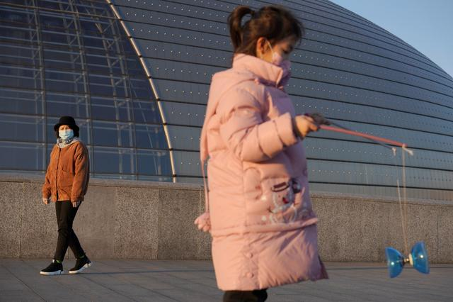A girl wearing a face mask plays with a diabolo near the National Centre for the Performing Arts, following an outbreak of the novel coronavirus in the country, in Beijing, China February 22, 2020. REUTERS/Stringer  NO RESALES. NO ARCHIVES.