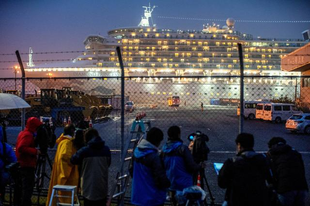 FILE PHOTO: A bus arrives near the cruise ship Diamond Princess, where dozens of passengers were tested positive for coronavirus, at Daikoku Pier Cruise Terminal in Yokohama, south of Tokyo, Japan, February 16, 2020. REUTERS/Athit Perawongmetha/File Photo
