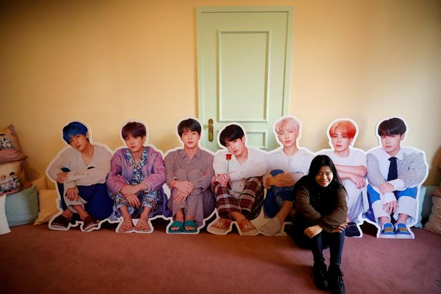 FILE PHOTO: A fan of K-pop idol boy band BTS poses for photographs with cut-out of BTS at a pop-up store selling BTS goods in Seoul, South Korea, December 24, 2019.     REUTERS/Kim Hong-Ji