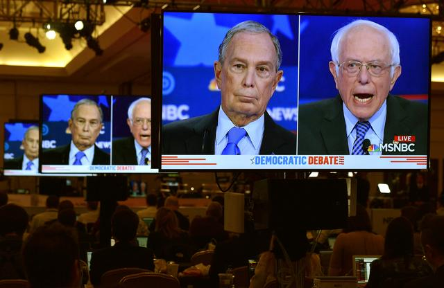 FILE PHOTO: Former New York City Mayor Mike Bloomberg and Senator Bernie Sanders are seen on video screens in the media filing center during the ninth Democratic 2020 U.S. Presidential candidates debate at the Paris Theater in Las Vegas, Nevada, U.S., February 19, 2020. REUTERS/David Becker/File Photo