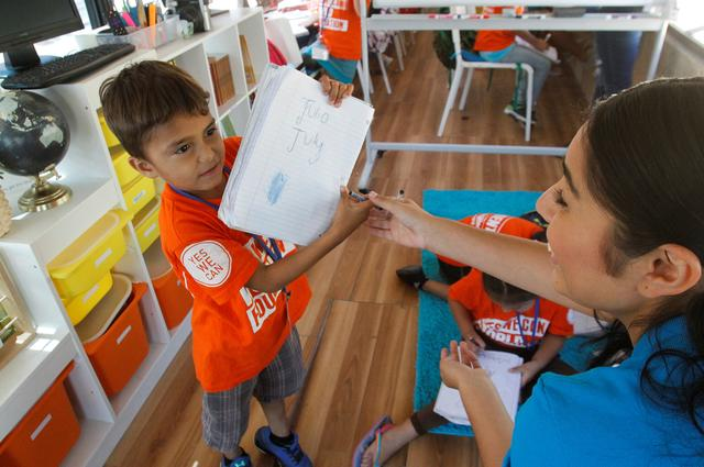 A migrant child shows his work to a teacher during English lessons at a bus converted in a classroom as part of Schools On Wheels program by California's 'Yes We Can' organisation, in Tijuana, Mexico August 2, 2019. Picture taken August 2, 2019. REUTERS/Jorge Duenes - RC153C05DAA0