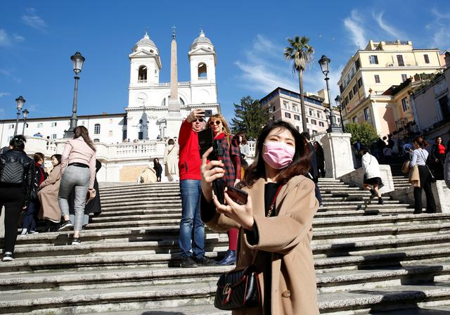 A tourist wearing protective a mask takes a selfie along the Spanish step in Rome, Italy, February 25, 2020. REUTERS/Remo Casilli