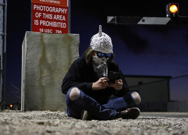 FILE PHOTO: A person looks at their phone at a gate to Area 51 as an influx of tourists responding to a call to 'storm' Area 51, a secretive U.S. military base believed by UFO enthusiasts to hold government secrets about extra-terrestrials, is expected in Rachel, Nevada, U.S. September 20, 2019. REUTERS/Jim Urquhart