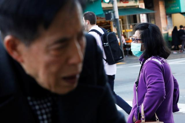 A woman wears a face mask standing on a corner in the Chinatown section of San Francisco, California, U.S., February 25, 2020.   REUTERS/Shannon Stapleton